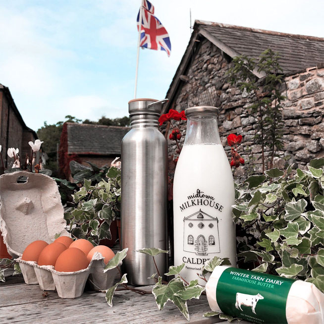 Eggs in a carton, milk in a midtown milkhouse glass bottle and cheese from Winter Tarn Dairy on a table outside. Union Jack flag flying in background